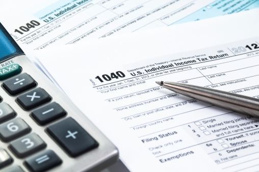 A picture of a 1040 tax return form next to a calculator.